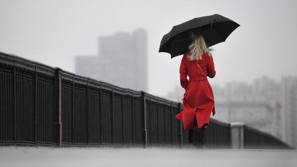 Женщина с зонтом идет по Крымскому мосту во время дождя в Москве