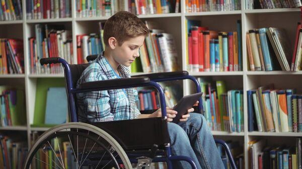 Школьник с ограниченными возможностями в школьной библиотеке