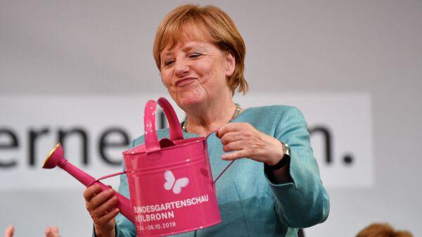 Канцлер Германии Ангела Меркель держит лейку, которую она получила в подарок во время предвыборного митинга Христианско-демократического союза в Хайльбронне, южная Германия. 16 августа 2017 года