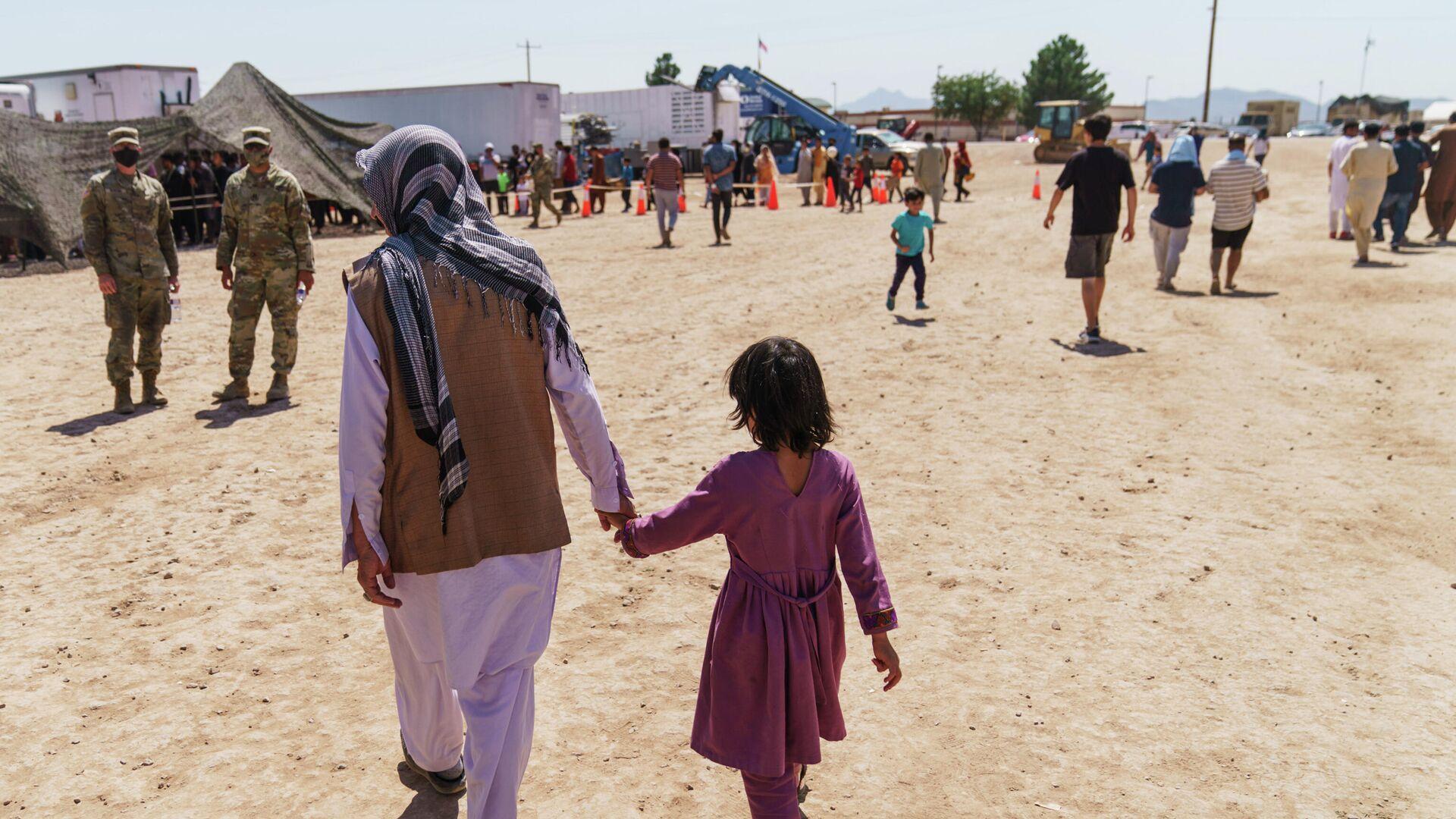Афганский беженец гуляет с ребенком на территории военной базы в США - РИА Новости, 1920, 28.09.2021