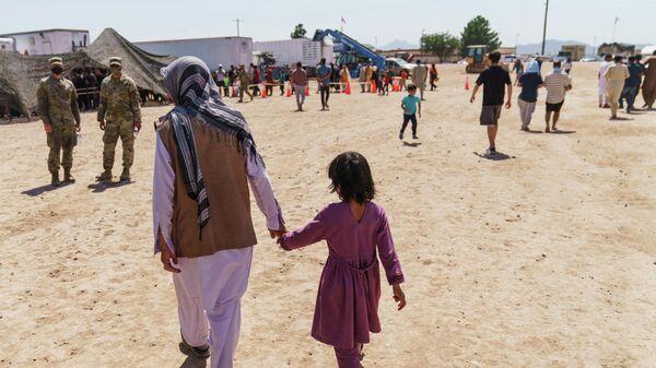 Афганский беженец гуляет с ребенком на территории военного комплекса Донья Ана в Нью-Мексико, США