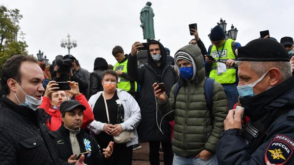 Участники встречи граждан с депутатами Госдумы и Мосгордумы от КПРФ разговаривают с сотрудником полиции на Пушкинской площади в Москве
