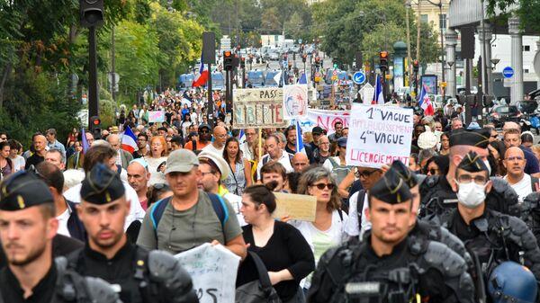 Участники во время акции против COVID-ограничений на одной из улиц в Париже