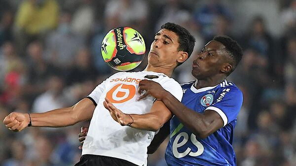 Lille's French midfielder Benjamin Andre (L) is challenged by Strasbourg's French midfielder Jean-Ricner Bellegarde during the French L1 football match between RC Strasbourg Alsace and Lille LOSC at Stade de la Meinau in Strasbourg, eastern France on September 25, 2021. (Photo by PATRICK HERTZOG / AFP)