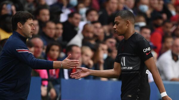 Paris Saint-Germain's French forward Kylian Mbappe greets Paris Saint-Germain's Argentinian head coach Mauricio Pochettino as he is substituted during the French L1 football match between Paris Saint-Germain (PSG) and Montpellier (MHSC) at The Parc des Princes stadium in Paris on September 25, 2021. (Photo by FRANCK FIFE / AFP)