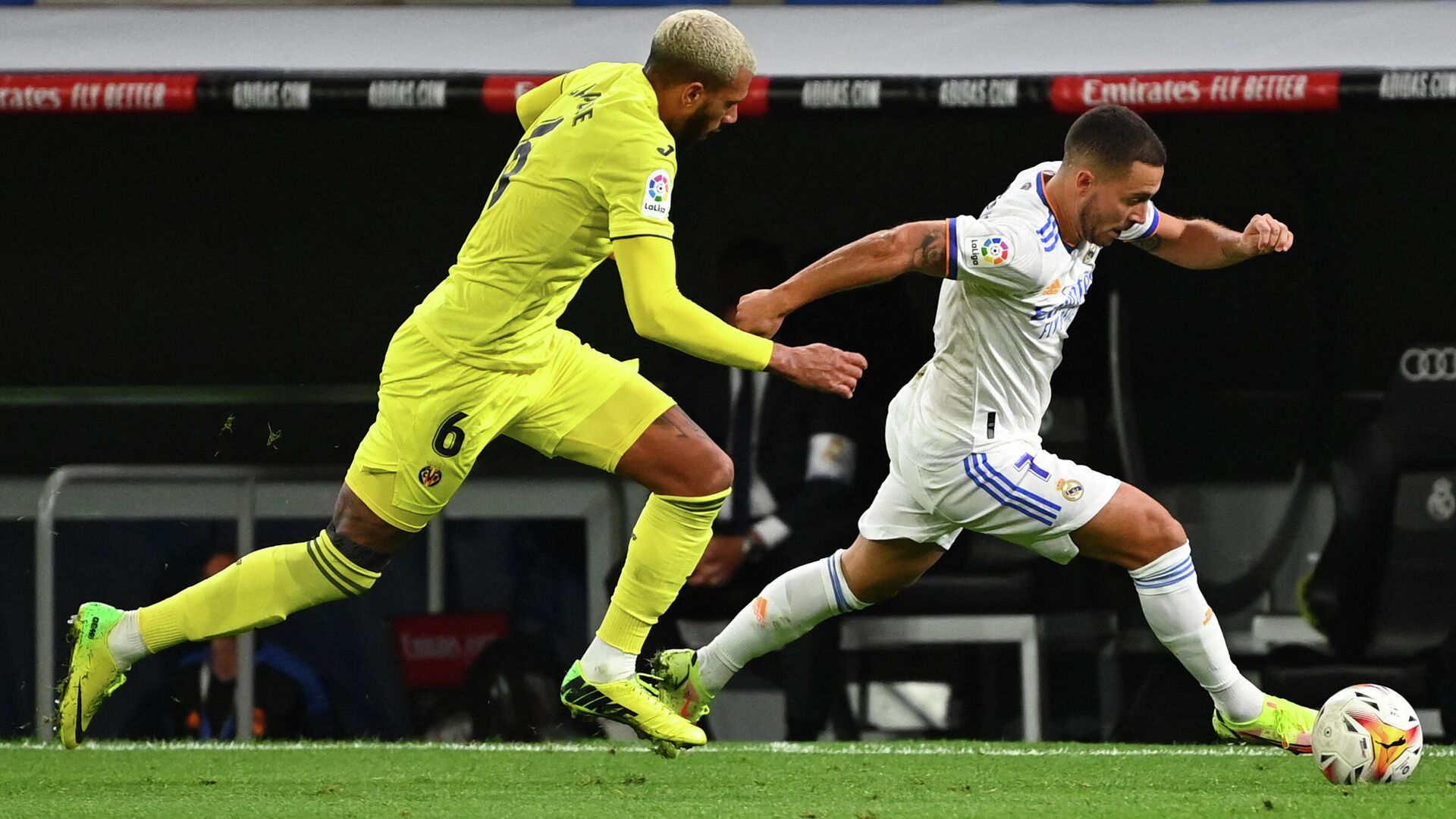 Villarreal's French midfielder Etienne Capoue (L) challenges Real Madrid's Belgian forward Eden Hazard during the Spanish League football match between Real Madrid and Villarreal CF at the Santiago Bernabeu stadium in Madrid on September 25, 2021. (Photo by GABRIEL BOUYS / AFP) - РИА Новости, 1920, 26.09.2021