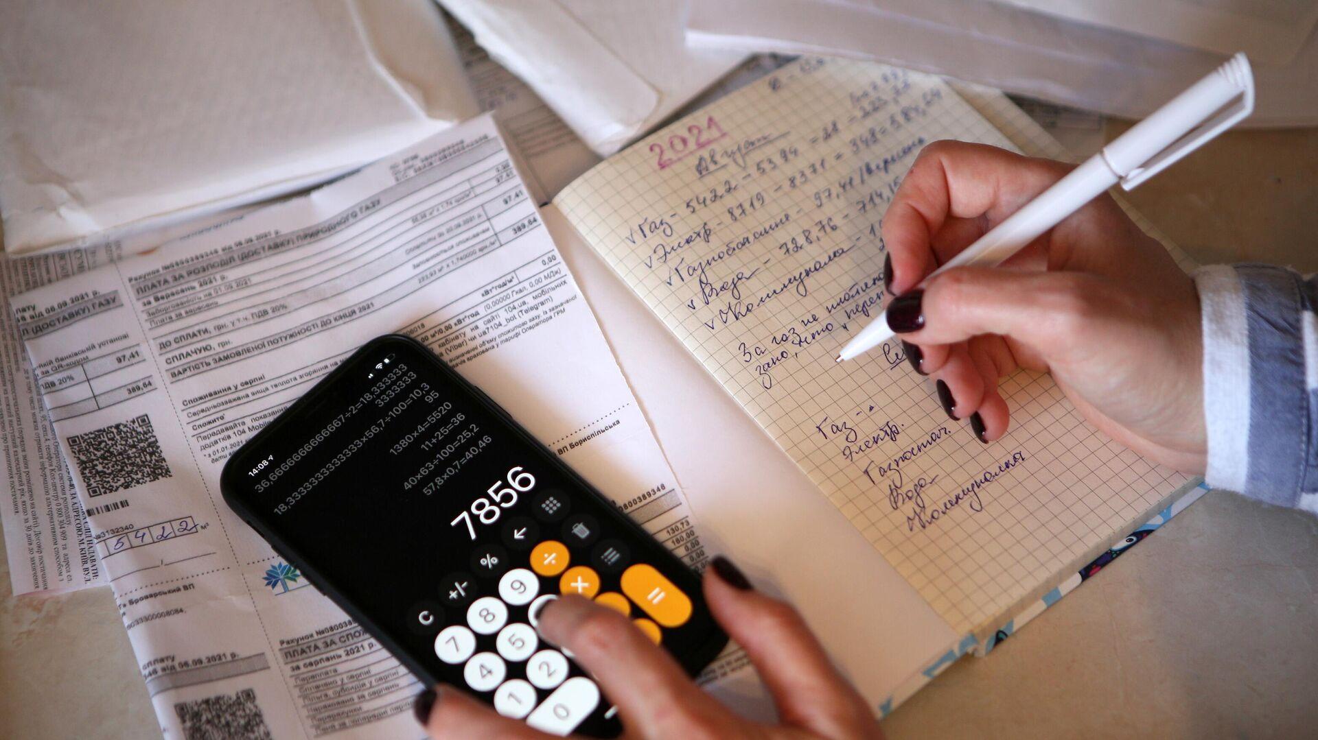 Девушка подсчитывает коммунальные платежи у себя дома - РИА Новости, 1920, 27.09.2021