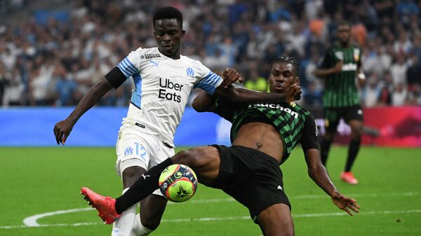 Marseille's Senegalese forward Bamba Dieng is tackled in the penalty area by Lens' French defender Christopher Maurice Wooh and obtains a penalty during the French L1 football match between Olympique Marseille (OM) and RC Lens at Stade Velodrome in Marseille, southern France on September 26, 2021. (Photo by Christophe SIMON / AFP)