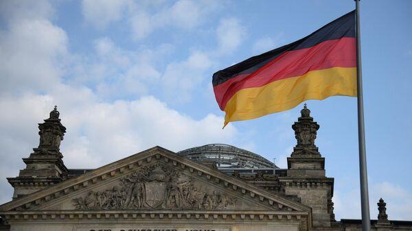 Национальный флаг Федеративной Республики Германии над зданием Будестага в Берлине