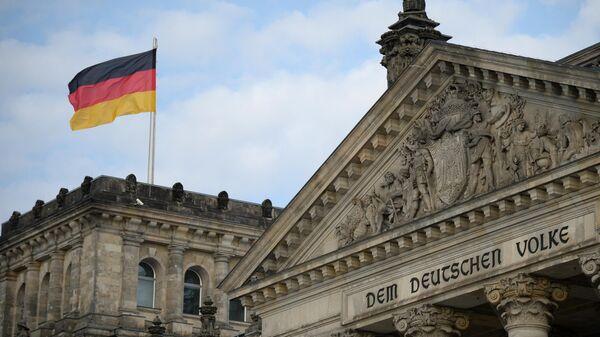 Национальный флаг Федеративной Республики Германии над зданием Будестага в Берлине в день выборов в парламент Германии