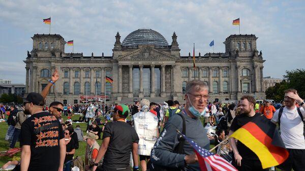 Жители Берлина на лужайке на площади Республики перед зданием Будестага в день выборов в парламент Германии