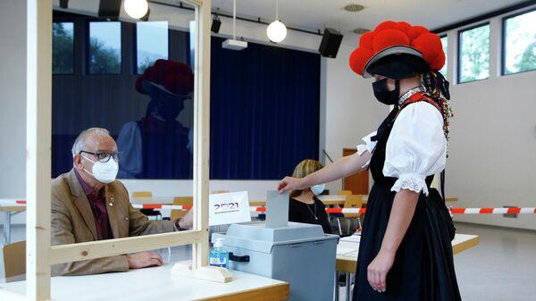Женщина в традиционном костюме голосует в Шварцвальде, Германия