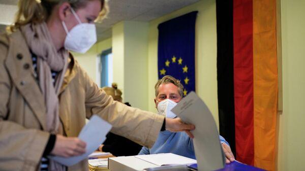 Женщина голосует на избирательном участке в Берлине, Германия