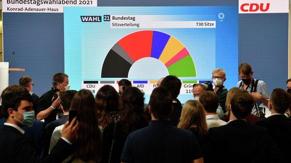 Сторонники и члены Христианско-демократического союза (ХДС) смотрят на результаты голосования в штаб-квартире Христианско-демократического союза в Берлине