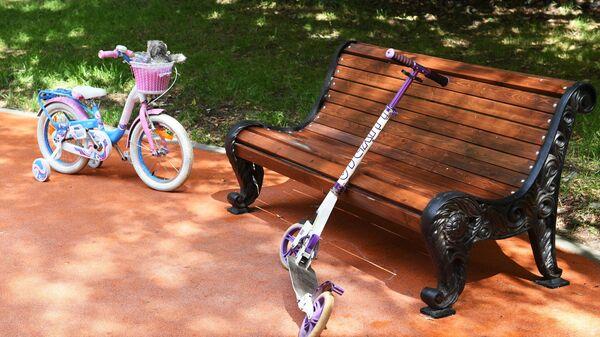 Детский велосипед и самокат возле скамейки в Грачевском парке