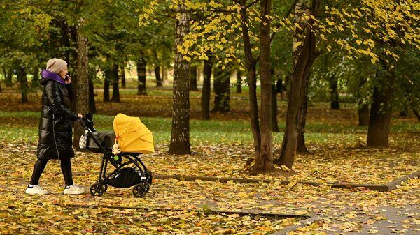 Женщина с коляской во время прогулки в парке Красная Пресня в Москве