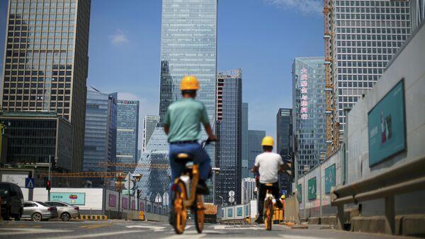 Мужчины проезжают на велосипедах мимо строительных площадок возле штаб-квартиры China Evergrande Group в Шэньчжэне, провинция Гуандун, Китай