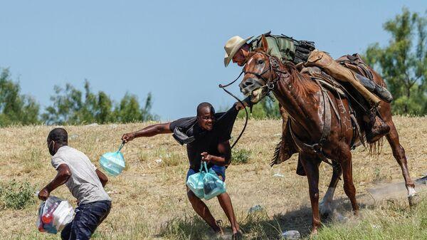 Служба Пограничного контроля США верхом на лошади ловят мигрантов из Гаити на берегу Рио-Гранде возле моста в городе Дель-Рио, штат Техас