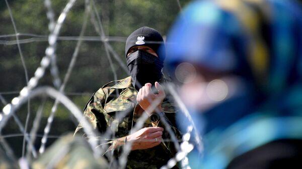 Польский пограничник наблюдает за лагерем беженцев из Афганистана на белорусско-польской границе.