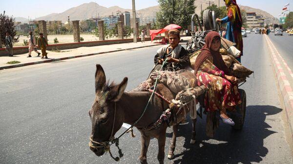 Местные жители едут на повозке по улице в Кабуле