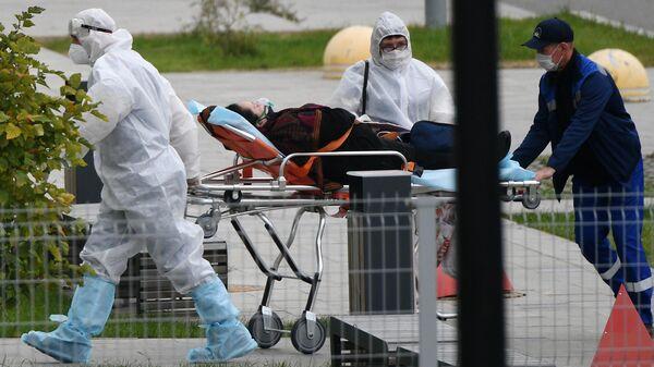 Бригада скорой медицинской помощи доставляет пациента в карантинный центр в Коммунарке