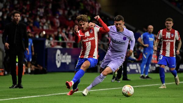Atletico Madrid's French midfielder Antoine Griezmann (L) fights for the ball with Barcelona's French defender Clement Lenglet during the Spanish League football match between Club Atletico de Madrid and FC Barcelona at the Wanda Metropolitano stadium in Madrid on October 2, 2021. (Photo by JAVIER SORIANO / AFP)