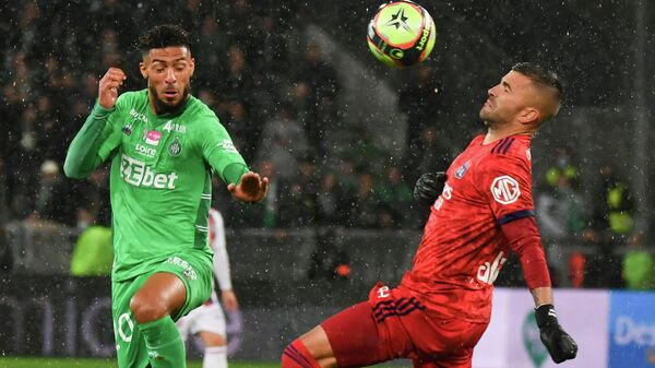 Saint-Etienne's Gabonese forward Denis Bouanga (L) fights for the ball with Lyon's Portuguese goalkeeper Anthony Lopes (R) during the French  football match between AS Saint-Etienne and Olympique Lyonnais at the Geoffroy Guichard stadium in Saint-Etienne, central France on October 3, 2021. (Photo by PHILIPPE DESMAZES / AFP)