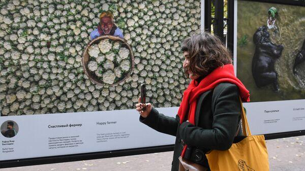 Девушка у фотографий на выставке работ финалистов фотоконкурса им. А. Стенина на Гоголевском бульваре в Москве