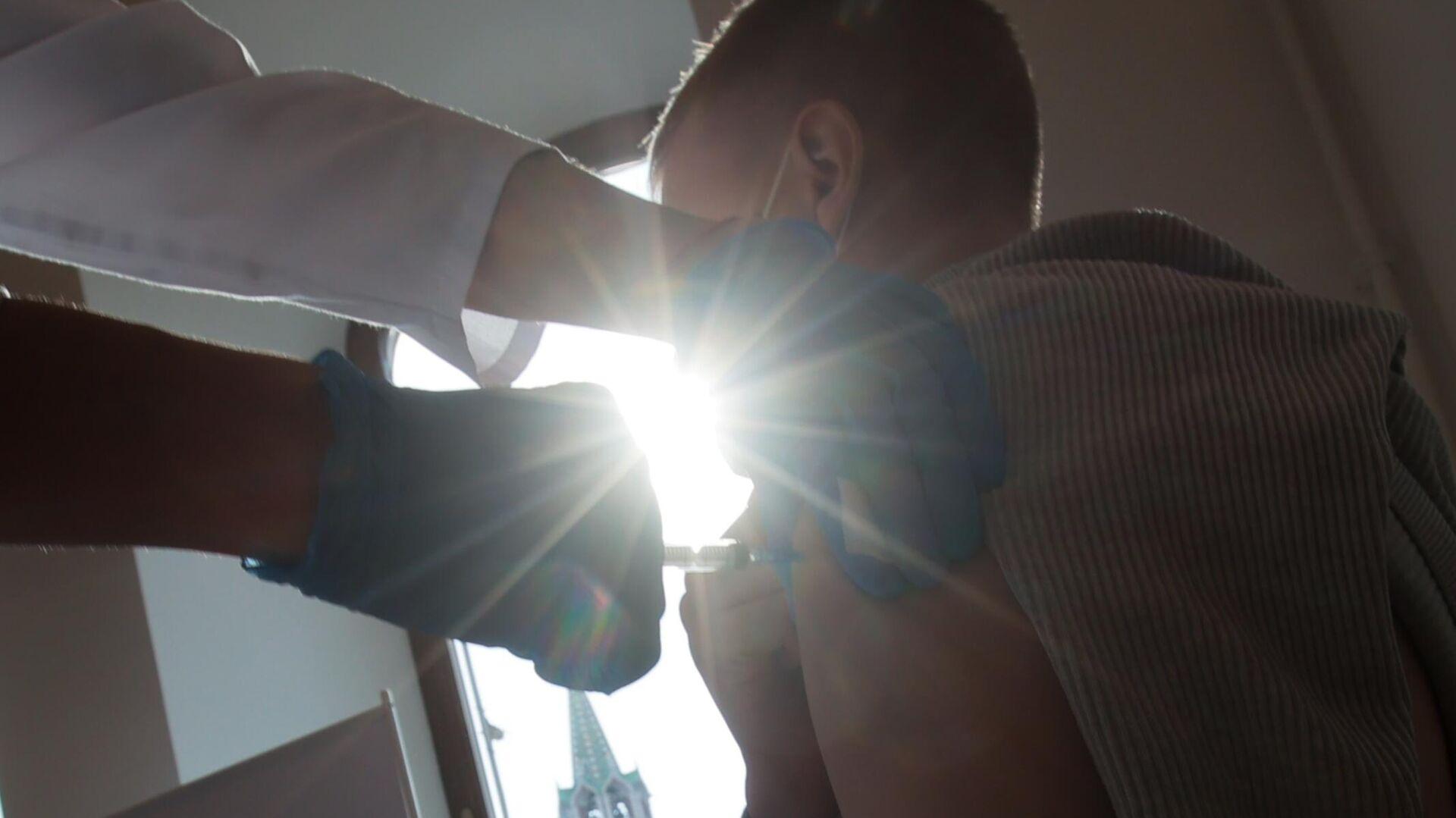 Молодой человек делает прививку в пункте вакцинации от COVID-19 - РИА Новости, 1920, 05.10.2021