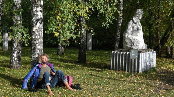 Мужчина сидит на солнце под деревом в парке искусств Музеон