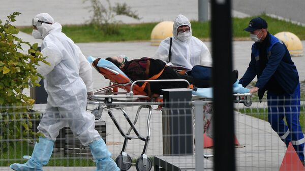 Бригада скорой медицинской помощи доставляет пациента в карантинный центр