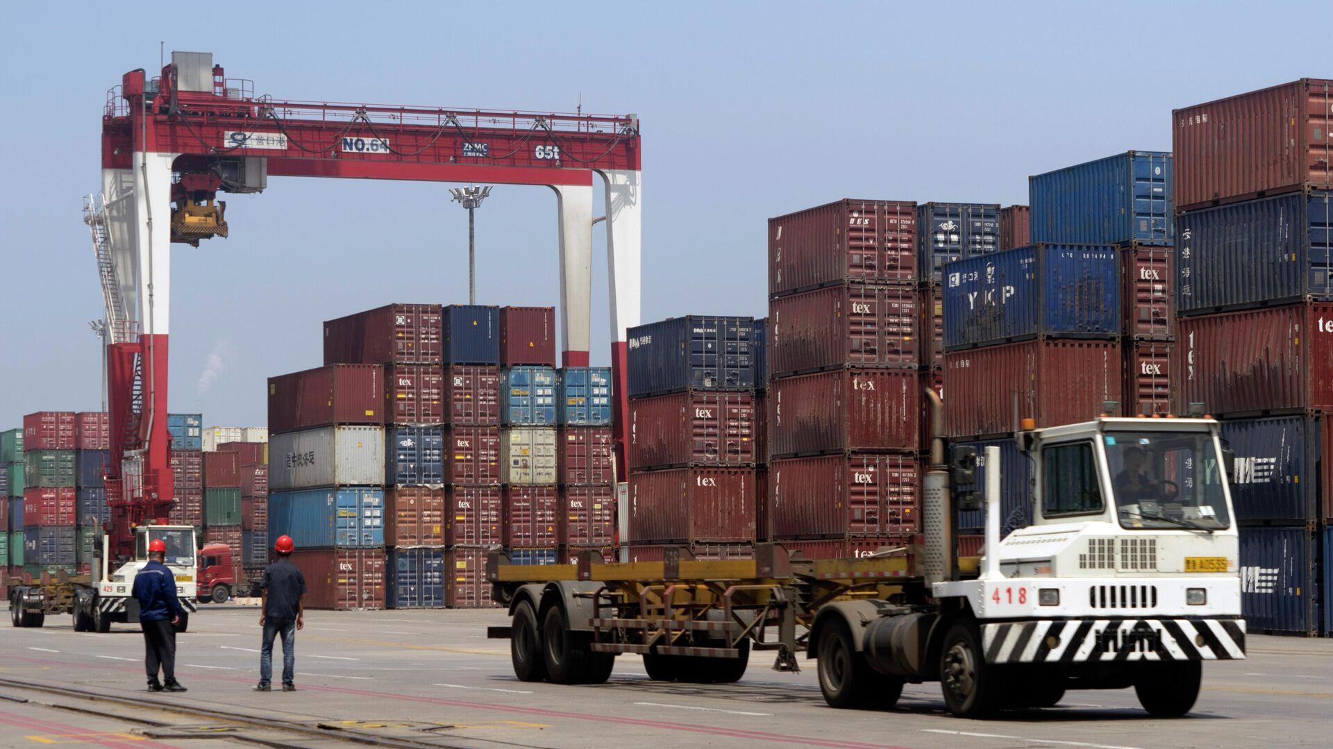 Грузовик проезжает мимо транспортных контейнеров в порту Инкоу в провинции Ляонин на северо-востоке Китая - РИА Новости, 1920, 05.10.2021