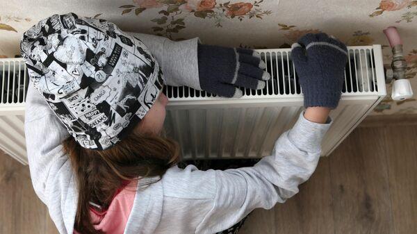 Девочка возле батареи у себя дома в Киеве, Украина