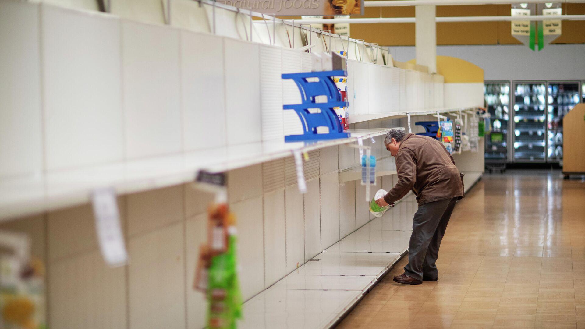 Мужчина берет с пустой полки пачку туалетной бумаги в супермаркете в Род-Айленд. - РИА Новости, 1920, 12.10.2021