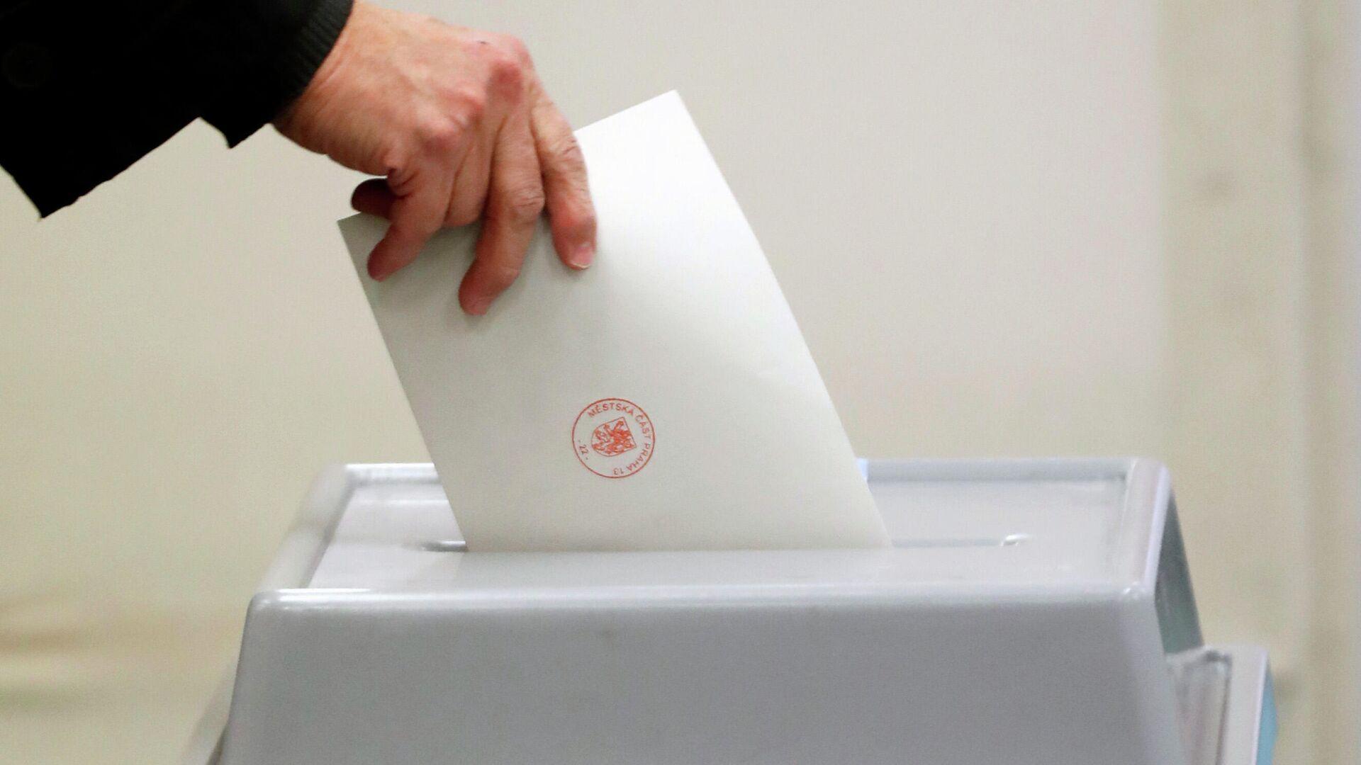Человек опускает бюллетень в избирательную урну в Чехии - РИА Новости, 1920, 10.10.2021