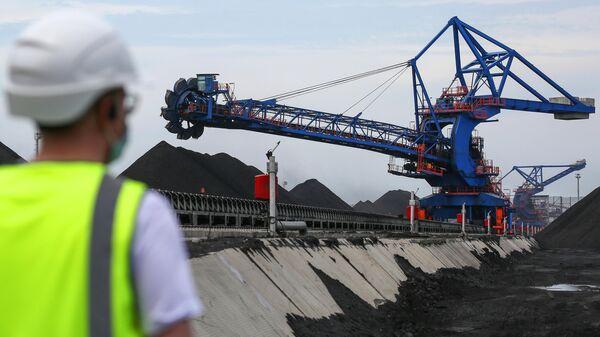 Сотрудник Таманского терминала навалочных грузов следит за работой стакера-реклаймера на складе угля