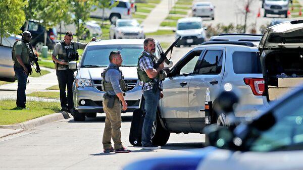 Сотрудники правоохранительных органов во время операции по задержанию подозреваемого в стрельбе в средней школе Timeberview в Арлингтоне