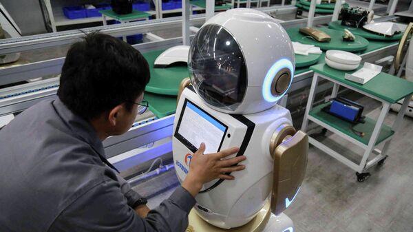 Рабочий на заводе заводе по производству промышленных роботов в Китае