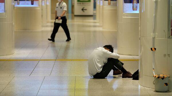 Мужчина на полу вокзала Токио