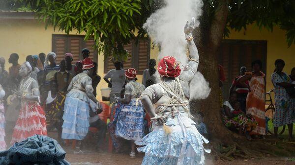 Комиана, традиционная жрица, проводит обряд во время церемонии очищения вдовы в Кот-д'Ивуаре
