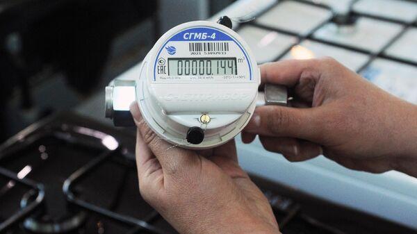 Продавец-консультант держит в руках газовый счетчик в магазине газового оборудования АО Газпром газораспределение Тамбов в Тамбове