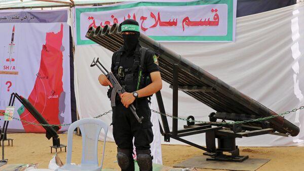 Вооруженный палестинец стоит рядом с ракетными установками в Газе