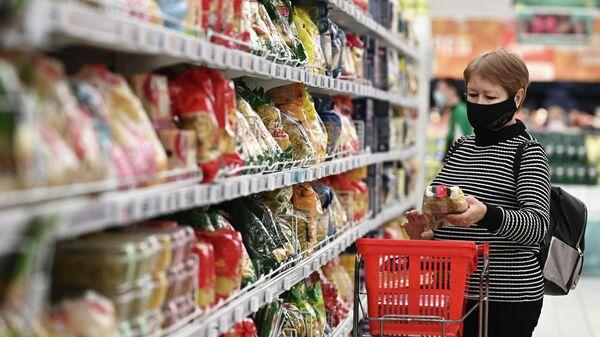 Покупатель в отделе макаронных изделий в гипермаркете Ашан