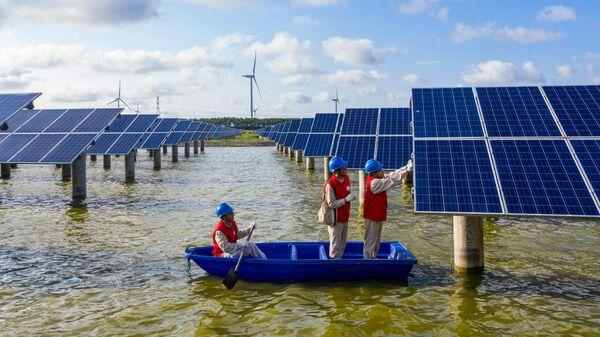 Электротехники проверяют солнечные панели электростанции в пруду в Хайане, Китай