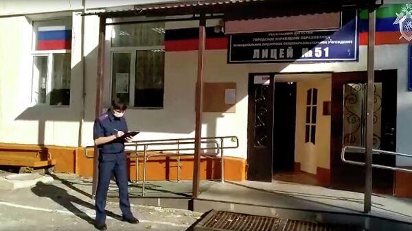 Сотрудник СК РФ у школы №51 Махачкалы, где произошло убийство учащегося. Кадр видео