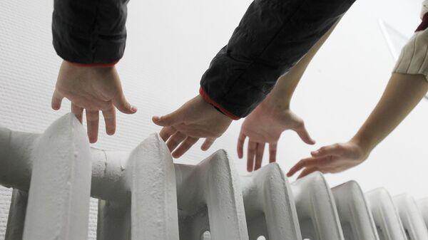 Жители Москвы держат руки над батареей