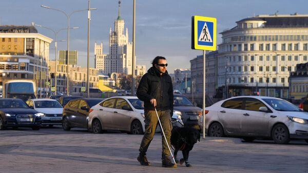Мужчина переходит дорогу на одной из улиц Москвы
