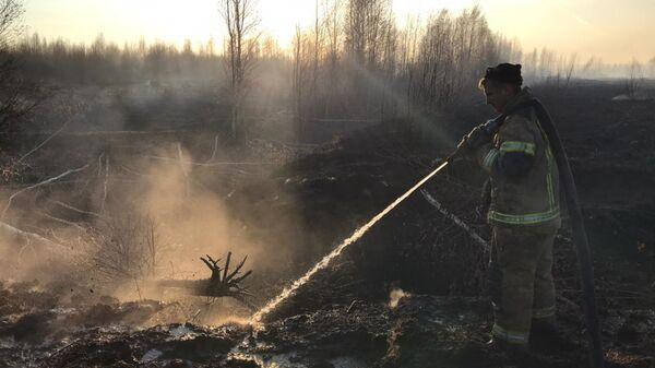Пожарный у тлеющего торфяника на юге Екатеринбурга