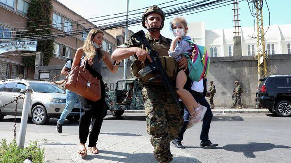 Военнослужащий с ребенком во время перестрелки в Бейруте