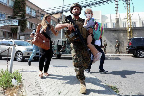 Военнослужащий помогает семье уйти с места митинга
